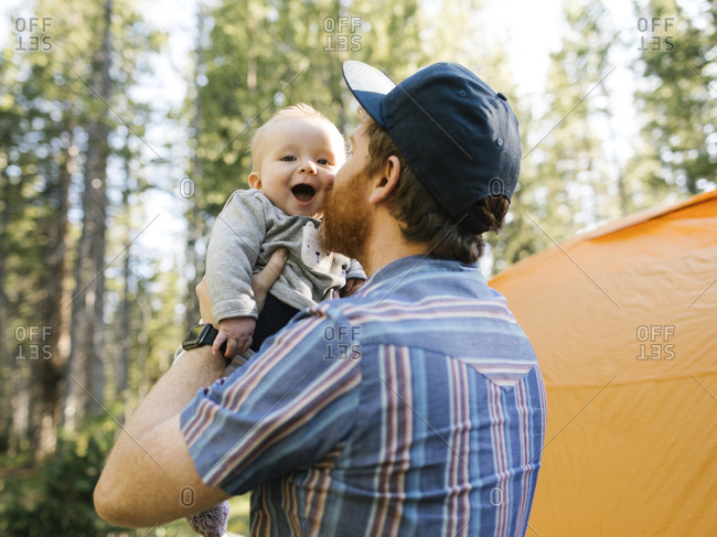 Man kissing baby son (6-11 months) in forest, tent in background, Wasatch Cache National Forest