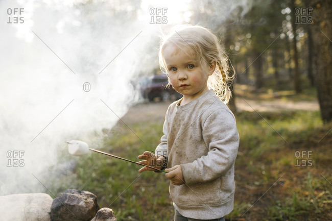 Portrait of girl (2-3) roasting marshmallow over campfire, Wasatch Cache National Forest