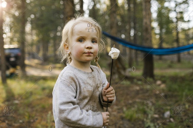 Portrait of girl (2-3) with marshmallow on stick in forest, Wasatch-Cache National Forest