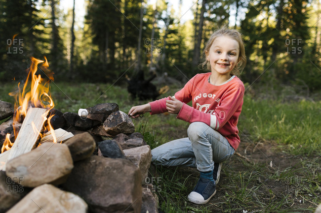 Portrait of smiling girl (6-7) roasting marshmallow above campfire, Wasatch Cache National Forest