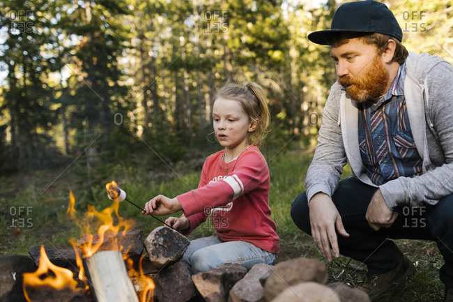 Man with daughter (6-7) roasting marshmallow above campfire, Wasatch Cache National Forest