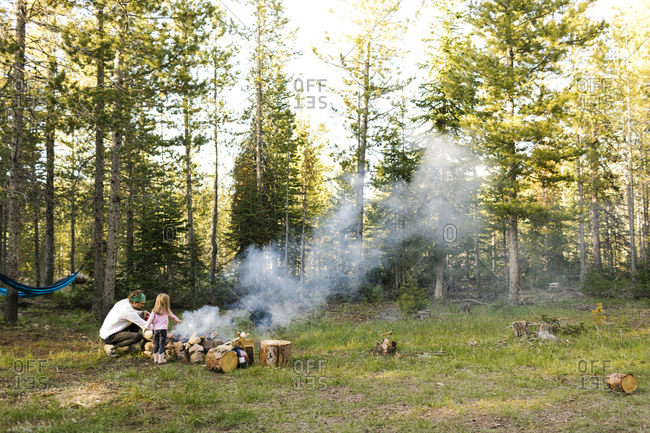 Father and daughter (4-5) at campfire in forest, Wasatch Cache National Forest