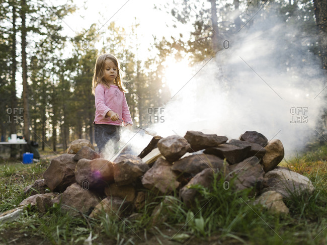 Girl (4-5) roasting marshmallow above campfire, Wasatch Cache National Forest