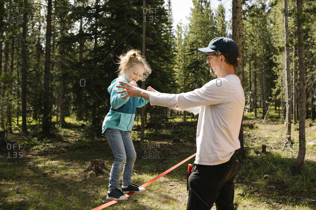 Father assisting daughter (2-3) walking on slackline in forest, Wasatch-Cache National Forest