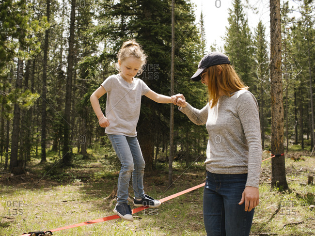 Mother assisting daughter (6-7) walking on slackline in forest, Wasatch-Cache National Forest
