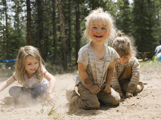 Three smiling girls (2-3, 4-5) playing in sand on camping, Wasatch-Cache National Forest
