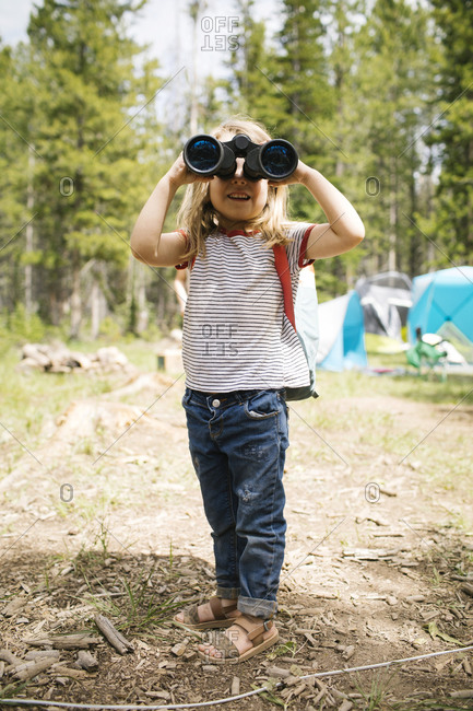 Girl (4-5) looking through binoculars in forest, Wasatch-Cache National Forest
