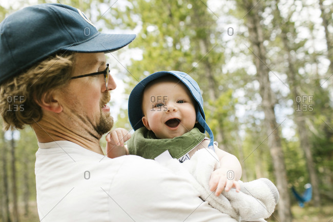 Father holding baby son (6-11 months) in forest, Wasatch-Cache National Forest