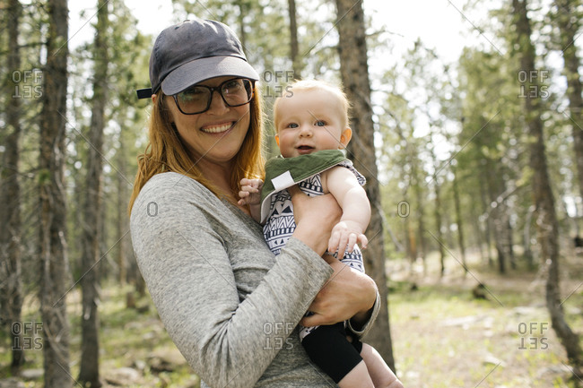Portrait of smiling woman with baby son (6-11 months) in forest, Wasatch-Cache National Forest