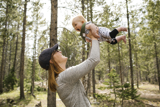 Smiling woman playing with baby son (6-11 months) in forest, Wasatch-Cache National Forest