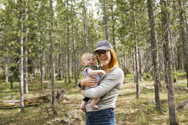 Portrait of smiling woman holding baby son (6-11 months) in forest, Wasatch Cache National Forest