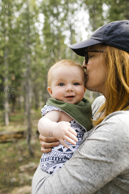 Woman kissing baby son (6-11 months) in forest, Wasatch-Cache National Forest