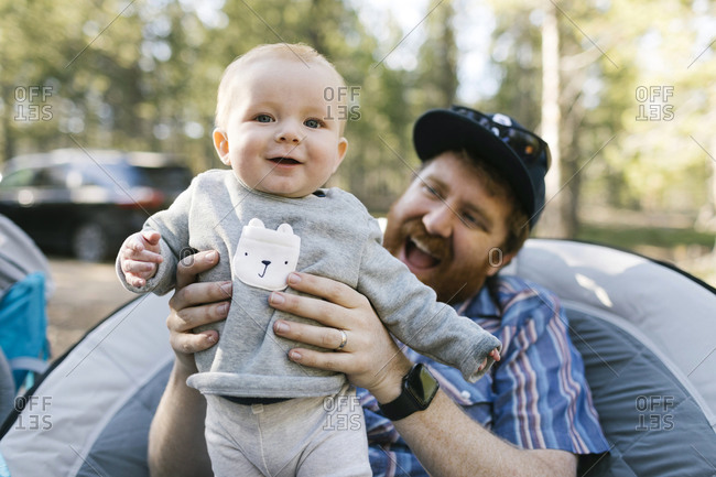 Smiling man holding baby son (6-11 months) on camping, Wasatch-Cache National Forest