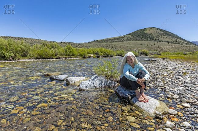 USA, Idaho, Sun Valley, Woman sitting on rock in river