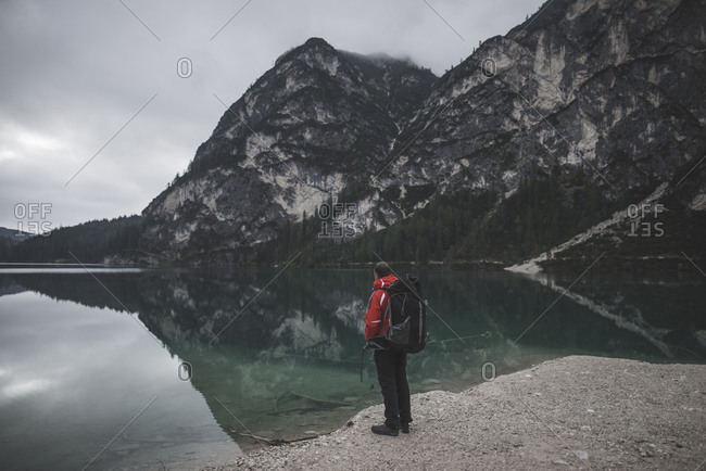 Italy, Pragser Wildsee, Dolomites, South Tyrol, Man looking at view standing near mountain lake