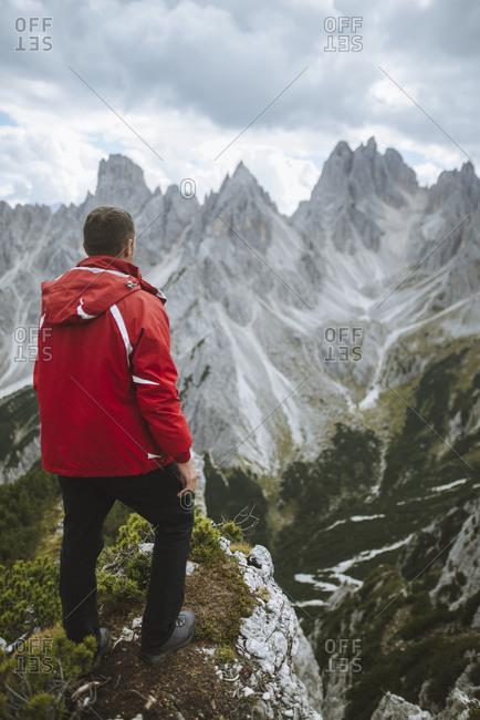Italy, South Tirol, Belluno, Sexten Dolomites, Cadini di Misurina, Man standing at the edge of precipice looking at view