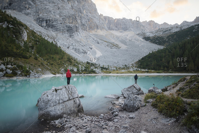 Italy, South Tyrol, Cortina d Ampezzo, lake Sorapis, Men standing on top of rock formations looking at view