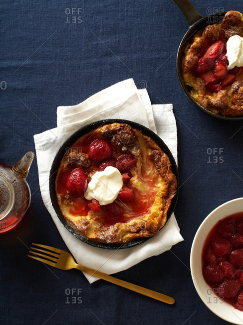 Dutch baby pancakes in various pans with poached strawberries and cream