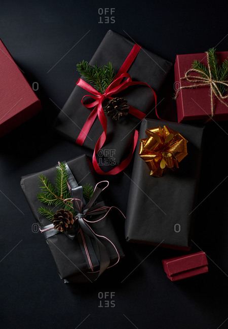 Wrapped and decorated gifts and boxes with presents on black background viewed from above