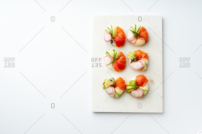 Sushi donuts with salmon and crunchy vegetables on marble cutting board. Top view with copy space.