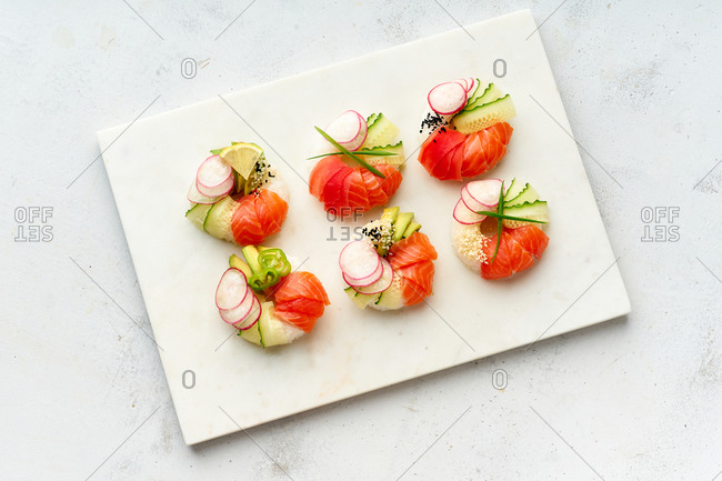 Sushi donuts with salmon and veggies on marble cutting board