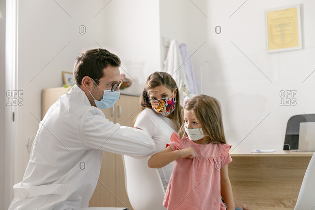 Medical practitioner and little patient in masks greeting each other with elbow bump