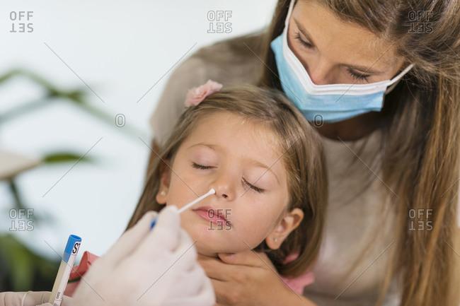 Doctor taking sample for coronavirus test from girl's nose