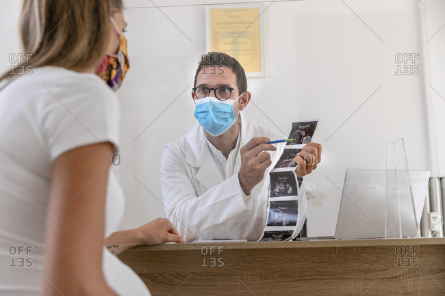 Man in medical uniform and mask showing sonogram to pregnant woman while sitting at table behind glass shield during epidemic in clinic