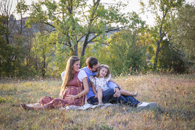Happy pregnant woman with loving husband and cute little daughter sitting together on grassy meadow during summer weekend in countryside in Italy