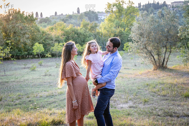Side view of happy pregnant woman with husband and adorable little daughter in countryside in Italy