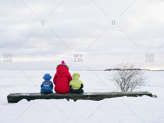 Mother with her sons sitting on a log watching sunset over the frozen ocean in Finland