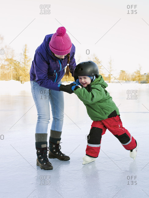 Mother teaching her son to ice skate