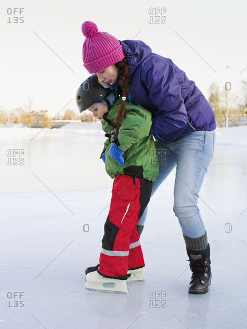 Mom teaching her young son to ice skate