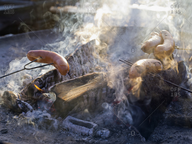 Barbequing sausages over a winter campfire