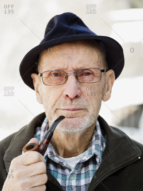 Old man holding his pipe and smiling