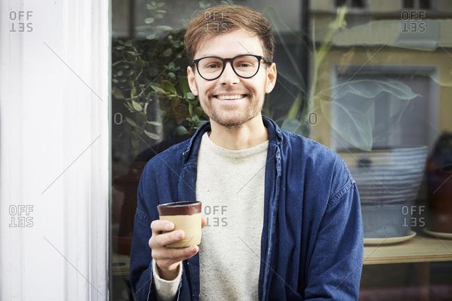 Portrait of smiling man having coffee outside art studio