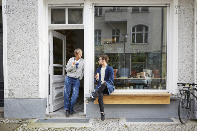 Male and female colleagues having coffee at entrance of art studio