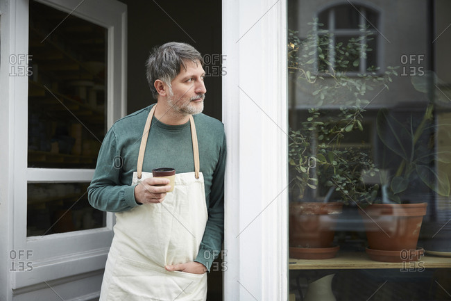Mature male owner looking away while having coffee at entrance of art studio