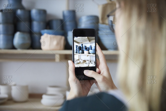 Cropped image of woman photographing earthenware with smart phone in art studio