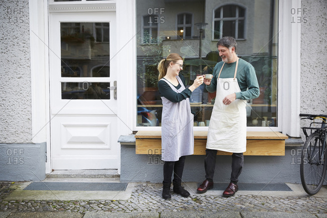 Smiling male and female colleagues toasting coffee outside art studio