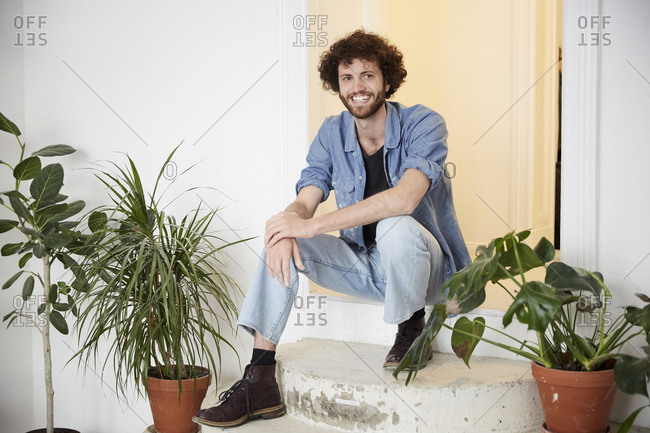 Full length portrait of smiling man sitting at entrance of art class