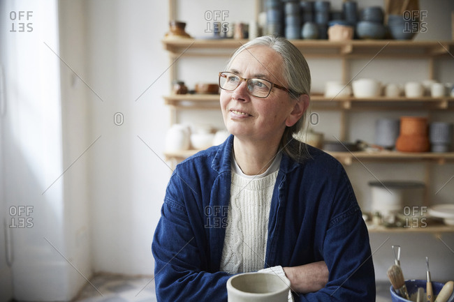 Thoughtful mature woman sitting in pottery class