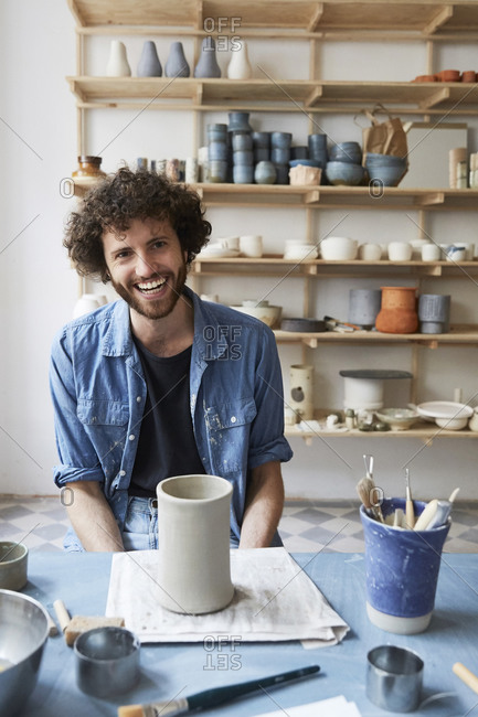 Portrait of smiling man sitting in pottery class
