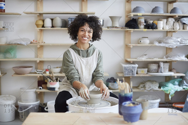 Portrait of smiling woman learning pottery in art studio