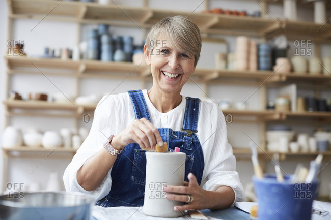 Portrait of smiling mature woman learning pottery in art studio