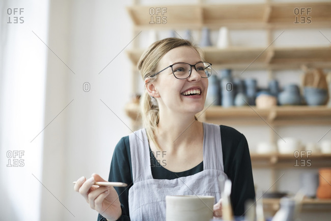 Smiling young woman looking up while learning pottery in art studio