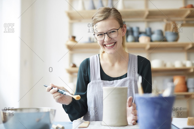 Portrait of smiling young woman learning pottery in art studio