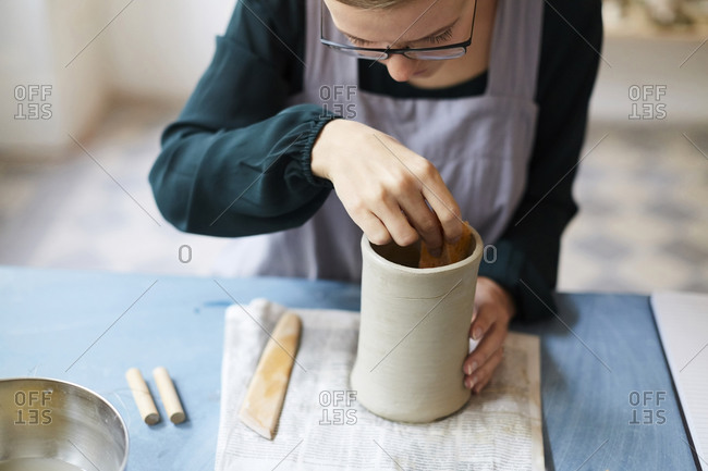 Young woman molding earthenware at table in art studio