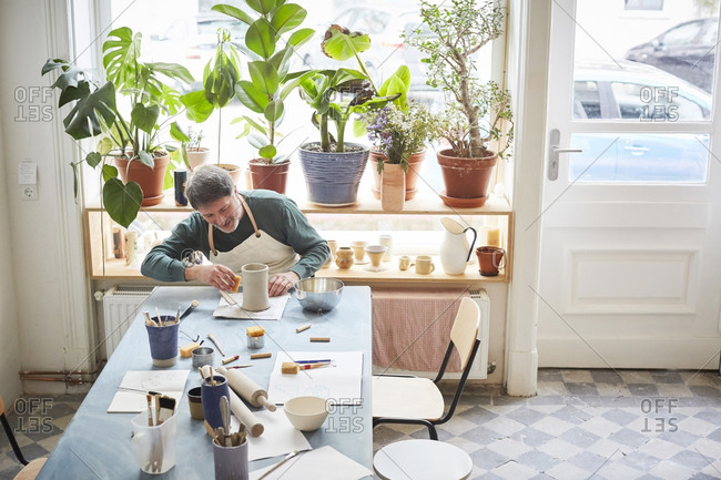 Mature man making craft product at table in pottery class