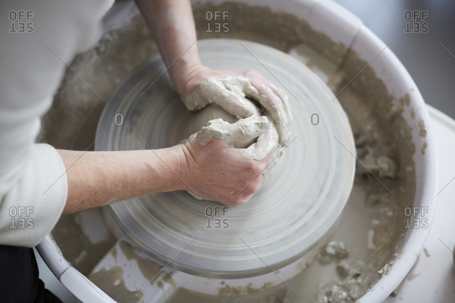 Cropped hands of woman molding pot in pottery class